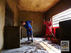 Volunteer helps local staff clean primate nighthouses at Chimfunshi Wildlife Orphanage, Zambia